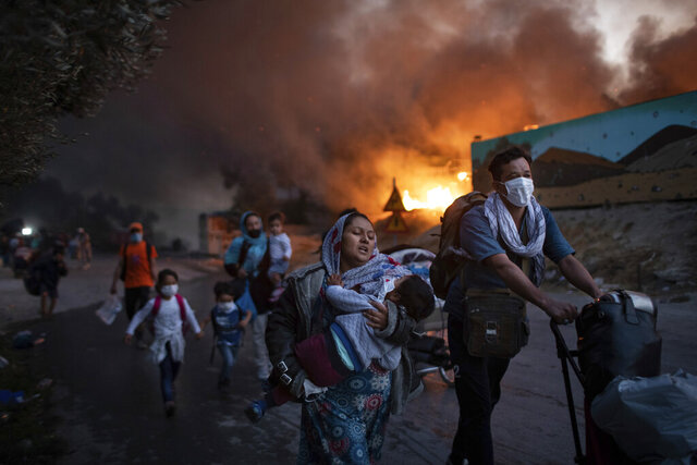 Migrants flee from the second fire in two days at the overcrowded Moria refugee camp on the island of Lesbos, Greece, on Sept. 9, 2020. (AP Photo/Petros Giannakouris)
