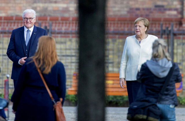 Federal President Frank-Walter Steinmeier and Federal Chancellor Angela Merkel are standing in front of the church of St. Peter and Paul for a group photo before an ecumenical service, Berlin, Germany, Saturday, Oct.3, 2020. Potsdam, as the capital of Brandenburg, will host this year's central celebrations of the Day of German Unity. (Christoph Soeder/dpa via AP)
