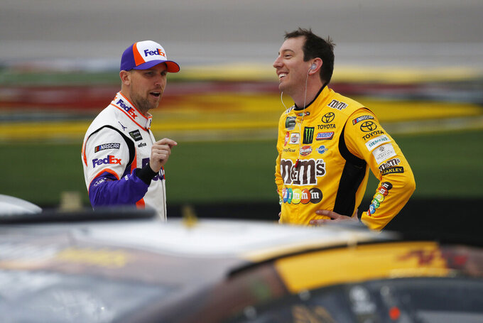 Denny Hamlin, left, and Kyle Busch talk in pit lane before qualifying for the NASCAR Cup Series auto race at Las Vegas Motor Speedway, Friday, March 1, 2019, in Las Vegas. (AP Photo/John Locher)