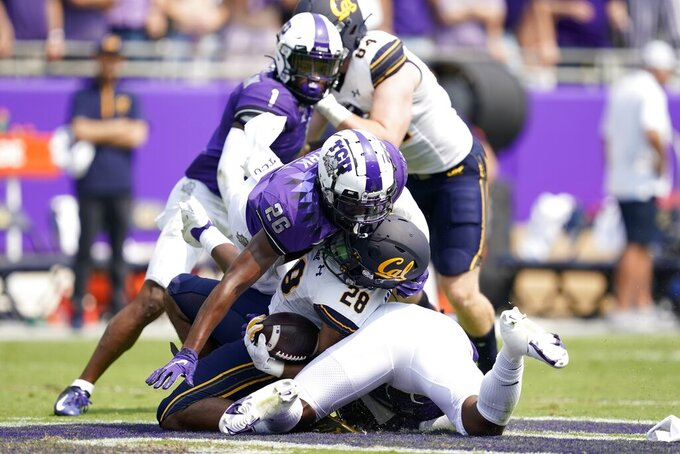 California running back Damien Moore (28) is stopped after a short run by TCU safety Bud Clark (26) and linebacker Dee Winters, bottom, in the first half of an NCAA college football game in Fort Worth, Texas, Saturday, Sept. 11, 2021. (AP Photo/Tony Gutierrez)