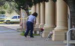 FILE - In this Aug. 29, 2017, file photo, a woman places flowers at the entrance of the Clovis-Carver Public Library in Clovis, N.M., a day after a deadly shooting. Nathaniel Jouett was convicted as an adult to two life sentences that will run concurrently plus 40 years in prison for carrying out the 2017 shooting at the Clovis library, killing two people under a sentence imposed Friday, Feb. 15, 2019, by a state district judge. (Adolphe Pierre-Louis/The Albuquerque Journal via AP, File)