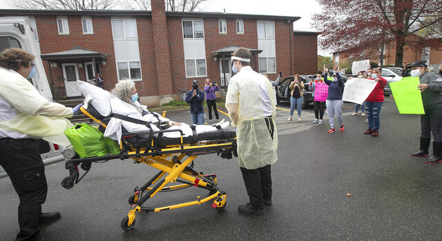 Friends and family of Nereida Diaz, 76, of Meriden, celebrate as Hunter's Ambulance EMTs Myles DiValentino, left, and Trevor Reitano return her home after recovering from COVID-19 complications at MidState Medical Center in Meriden, Conn. Thursday, April 30, 2020. (Dave Zajac/Record-Journal via AP)
