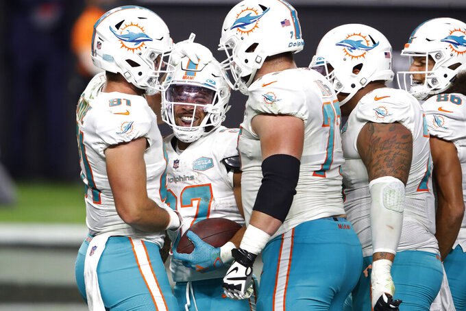 Miami Dolphins running back Myles Gaskin, second from left, celebrates after scoring a touchdown against the Las Vegas Raiders during the second half of an NFL football game, Saturday, Dec. 26, 2020, in Las Vegas. (AP Photo/Steve Marcus)