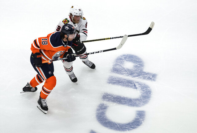 Edmonton Oilers' James Neal (18) and Chicago Blackhawks' Drake Caggiula (91) battle for the puck during the second period of an NHL Stanley Cup playoff hockey game in Edmonton, Alberta, Saturday, Aug. 1, 2020. (Jason Franson/The Canadian Press via AP)