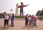 With the famous giant Big Tex as the background, families pose for photos during a drive-thru visit to Fair Park in Dallas, Saturday, Sept. 19, 2020. Although the State Fair of Texas was canceled this year due to COVID-19, fair organizers are holding drive-thru visits starting this weekend. (AP Photo/LM Otero)