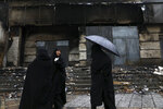 Women walk past a building damaged during recent protests, in Shahriar, Iran, some 40 kilometers (25 miles) southwest of the capital, Tehran, Wednesday, Nov. 20, 2019. Protests over government-set gasoline prices rising struck at least 100 cities and towns, spiraling into violence that saw banks, stores and police stations attacked and burned. (AP Photo/Vahid Salemi)