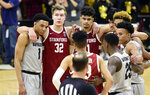 Colorado and Stanford players gather to say a prayer for Stanford's Oscar Da Silva, who had hit his head on the floor in a collision during the second half of an NCAA college basketball game Saturday, Feb. 8, 2020, in Boulder, Colo. (AP Photo/Cliff Grassmick)