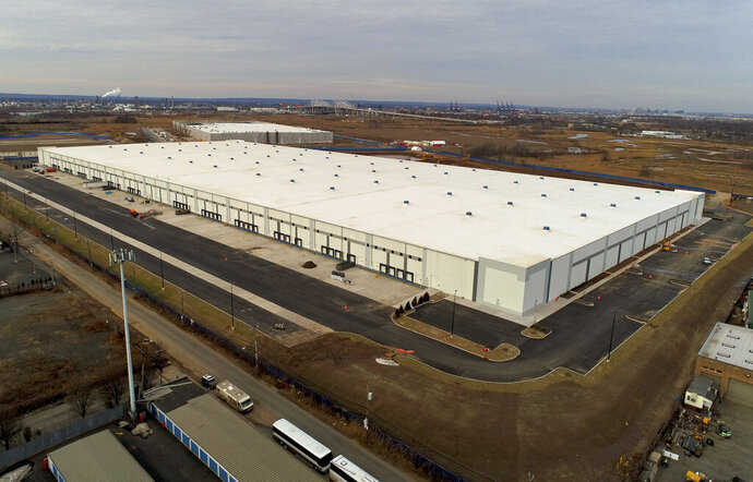 FILE - In this Jan. 27, 2018, file photo 975,000 square foot warehouse sits in Staten Island, New York. Warehouse properties are surging in value as people increasingly shop online and the popularity of quick delivery surges. Controlling warehouses in multiple locations allows companies like Amazon.com to package, ship and deliver goods often within hours of an order. (AP Photo/Julie Jacobson, File)
