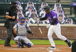 Colorado Rockies' Nolan Arenado reacts after striking out against Los Angeles Dodgers starting pitcher Alex Wood, while catcher Austin Barnes, center, and home plate umpire Mark Ripperger watch during the first inning of a baseball game Friday, Sept. 18, 2020, in Denver. (AP Photo/David Zalubowski)