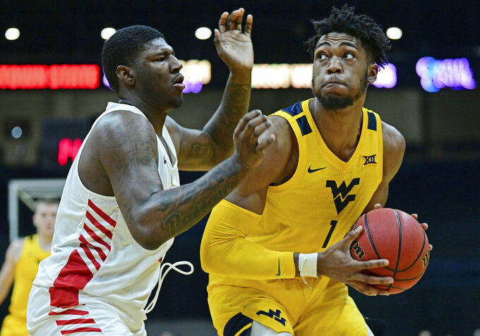 West Virginia forward Derek Culver (1) is guarded by Youngstown State guard Tyler Foster (1) during the second half of an NCAA college basketball game, Saturday, Dec. 21, 2019, in Youngstown, Ohio. West Virginia won 75-64. (AP Photo/David Dermer)