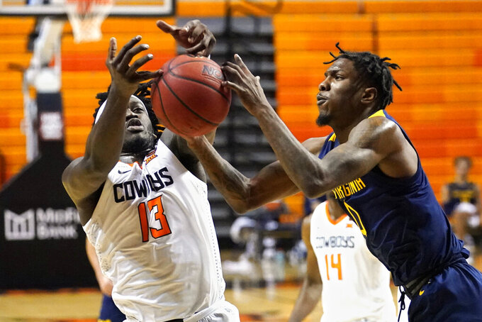 Oklahoma State guard Isaac Likekel (13) and West Virginia guard Kedrian Johnson (0) reach for the ball in the first half of an NCAA college basketball game Monday, Jan. 4, 2021, in Stillwater, Okla. (AP Photo/Sue Ogrocki)