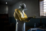 In this photo taken Tuesday, Nov. 6, 2018 and made available Tuesday, Dec. 4, 2018, a health worker is seen putting on his personal protective equipment (PPE) before entering the red zone of a Medecins Sans Frontieres (MSF) supported Ebola treatment centre in Bunia, Congo. Congo's deadly Ebola outbreak is now the second largest in history, behind the devastating West Africa outbreak that killed thousands a few years ago, according to the World Health Organization. (John Wessels/Medecins Sans Frontieres via AP)