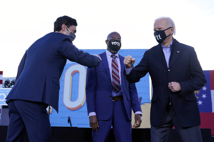 President-elect Joe Biden campaigns in Atlanta, Monday, Jan. 4, 2021, for Senate candidates Raphael Warnock, center, and Jon Ossoff, left. (AP Photo/Carolyn Kaster)
