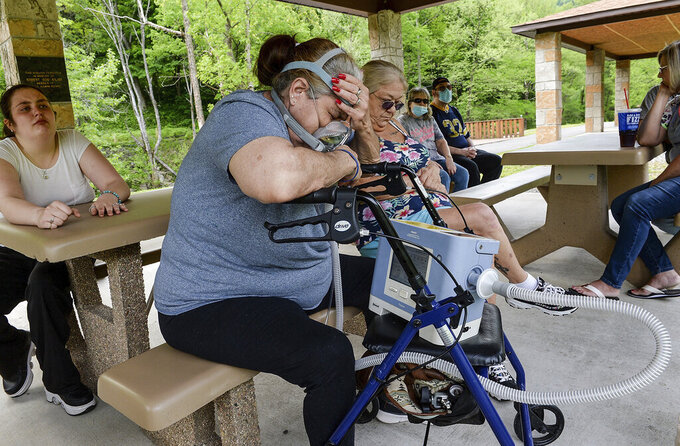 Becky Rechtenwald uses a portable ventilator to help her breathe while attending a community meeting May 18, 2021 in Eunice, WV, with her granddaughter, Alleson Sneed, 18, left, about the nearby coal mine. Rechtenwald is now living with her sister Kathy Slate (sitting next to her) in Elkview, driven from Eunice by what residents say is worsening coal dust pollution there. (Chris Dorst/ Charleston Gazette-Mail via AP)