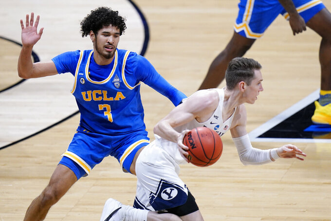 BYU guard Spencer Johnson (20) drives past UCLA guard Johnny Juzang (3) during the first half of a first-round game in the NCAA college basketball tournament at Hinkle Fieldhouse in Indianapolis, Saturday, March 20, 2021. (AP Photo/AJ Mast)