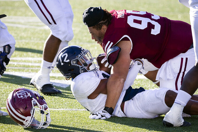 Massachusetts defensive lineman Hugo Klages (99) loses his helmet while tackling Georgia Southern running back Wesley Kennedy III (12) during the first half of an NCAA football game, Saturday, Oct. 17, 2020, in Statesboro, Ga. (AP Photo/Stephen B. Morton)
