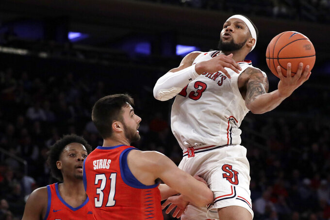 St. John's forward Marvin Clark II (13) goes up for a shot against DePaul guard Max Strus (31) and forward Femi Olujobi during the first half of an NCAA college basketball game in the Big East men's tournament Wednesday, March 13, 2019, in New York. (AP Photo/Julio Cortez)