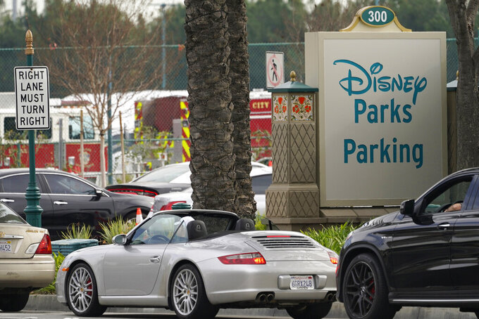 FILE - In this Jan. 13, 2021, file photo, vehicles queue up outside the Disneyland Resort parking lot for a COVID-19 vaccine in Anaheim, Calif. California has closed some vaccination centers and delayed appointments following winter storms elsewhere in the country that hampered the shipment of doses. Orange County shut its large-scale vaccination site at Disneyland through Monday, Feb. 22, 2021, after a shipment of Moderna COVID-19 vaccine doses didn't arrive this week. (AP Photo/Damian Dovarganes, File)