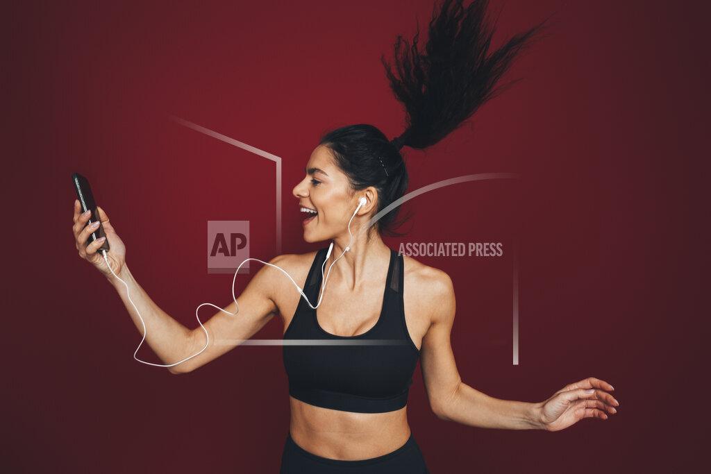 Female athlete jumping while listening music through smart phone