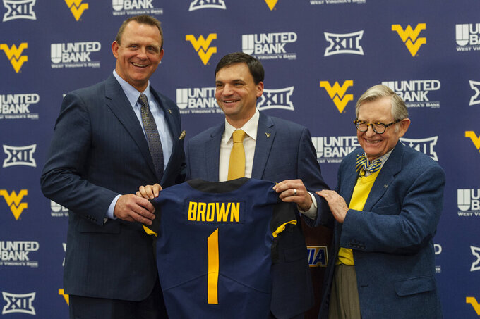 West Virginia University's new NCAA college football head coach Neal Brown holds up his team jersey with Director of Athletics Shane Lyons, left, and University President E. Gordon Gee at a press conference inside the Milan Puskar Center in Morgantown, W.Va., Thursday, Jan. 10, 2019. (Craig Hudson/The Charleston Gazette-Mail via AP