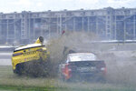 Christopher Bell (20) and Daniel Suarez (99) slide out during a massive crash caused by a piece of curbing during a NASCAR Series auto race at Indianapolis Motor Speedway, Sunday, Aug. 15, 2021, in Indianapolis. (Randy Crist/The Indianapolis Star via AP)