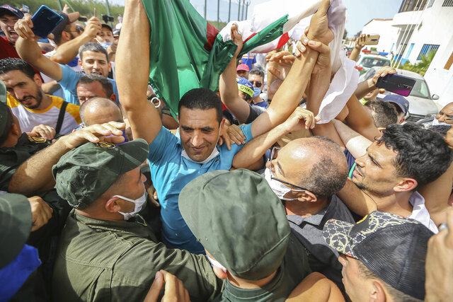 Activist Karim Tabbou holds a Algerian flag is greeted by supporters as he is released from the prison of Kolea, west of Algiers, Algeria, Thursday, July 2, 2020. Activists Karim Tabbou and Amira Bouraoui have been released from the prison of Kolea, west of Algiers, following decisions from Algerian courts. (AP Photo/Anis Belghoul)