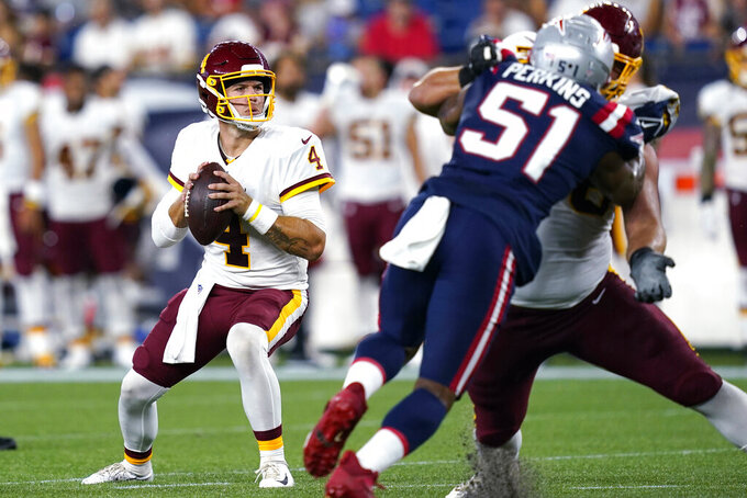 Washington Football Team quarterback Taylor Heinicke (4) looks to pass the ball during the first half of the team's preseason NFL football game against the New England Patriots, Thursday, Aug. 12, 2021, in Foxborough, Mass. (AP Photo/Elise Amendola)