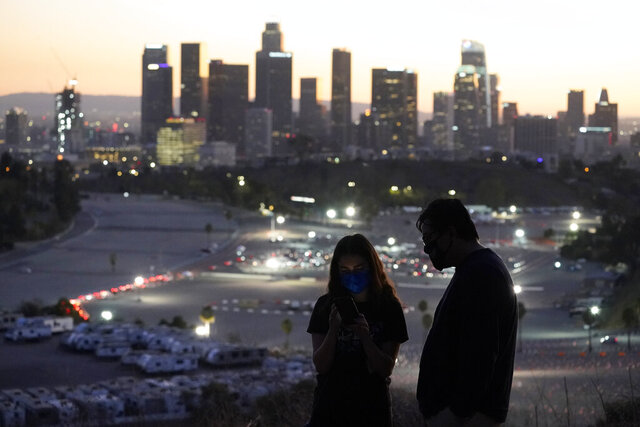 Visitors wear masks at a lookout point over at a COVID-19 vaccination site at Dodger Stadium Friday, Jan. 15, 2021, in Los Angeles. (AP Photo/Marcio Jose Sanchez)