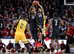Cincinnati forward Tre Scott (13) and guard Jarron Cumberland (34) grab a long pass intended for Wichita State forward Trey Wade (5) in the second half of an NCAA college basketball game Sunday, Feb. 23, 2020, in Cincinnati. (Albert Cesare/The Cincinnati Enquirer via AP)