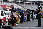 Crew members works on cars along pit road prior to qualifying for a NASCAR Cup Series auto race at Charlotte Motor Speedway Sunday, May 24, 2020, in Concord, N.C. (AP Photo/Gerry Broome)