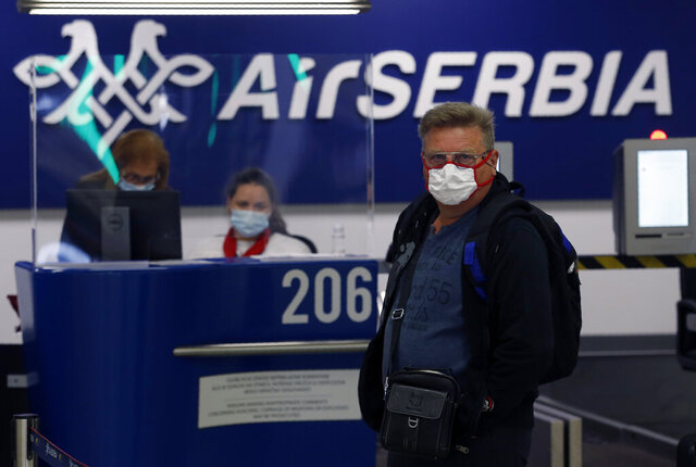 A passenger waits to check his luggage at Belgrade Nikola Tesla Airport, Serbia, Thursday, May 21, 2020. Serbia's national carrier Air Serbia has resumed commercial flights as the government eased the lockdown against the new coronavirus. Crisis authorities have said the situation in the country has stabilized despite virus clusters in the southern area. (AP Photo/Darko Vojinovic)