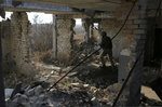 FILE - In this Nov. 18, 2019, file photo, a Ukrainian soldier takes his front line position in a destroyed building in the town of Avdiivka in the Donetsk region, Ukraine. For new Ukrainian President Volodymyr Zelenskiy, a summit meeting with Russia, France and Germany marks a decisive moment in his push to end more than five years of fighting with Moscow-backed separatists in the eastern part of his country. (AP Photo/Vitali Komar, File)