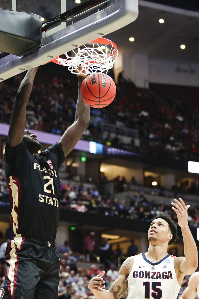 Florida State center Christ Koumadje, left, dunks as Gonzaga forward Brandon Clarke watches during the second half an NCAA men's college basketball tournament West Region semifinal Thursday, March 28, 2019, in Anaheim, Calif. (AP Photo/Jae C. Hong)