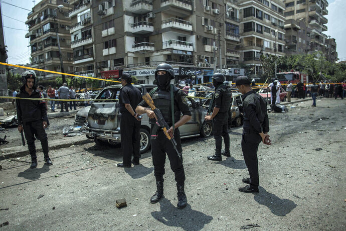 FILE -- In this June 29, 2015 file photo, Egyptian policemen stand guard at the site of a bombing that killed Egypt's top prosecutor, Hisham Barakat, who oversaw cases against thousands of Islamists, in Cairo. On Wednesday, Feb. 20, 2019 Egypt executed nine suspected Muslim Brotherhood members convicted of involvement in the 2015 assassination of Barakat, security officials said. The nine were found guilty of taking part in the bombing that killed Barakat, the first assassination of a senior official in Egypt in a quarter century. (AP Photo/Eman Helal, File)