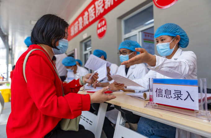In this photo released by Xinhua News Agency, a woman registers information for COVID-19 vaccination at the Jingcheng Hospital in Ruili city in southwestern China's Yunnan Province, April 1, 2021. The Chinese border city hit by a fresh outbreak of COVID-19 this week began a five-day drive Friday to vaccinate its entire population of 300,000 people. (Chen Xinbo/Xinhua via AP)