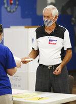Pole worker Bob Tipton hands a ballot to a voter during voting at precinct 61 in Edmond, Tuesday, June 30, 2020. (Doug Hoke/The Oklahoman via AP)