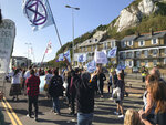 Extinction Rebellion protesters occupy one side of a dual carriageway at the port of Dover, England, Saturday Sept. 21, 2019. Traffic around the Port of Dover, England's major sea connection with France, has been disrupted as a result of a protest by environmental activists. Activists from Extinction Rebellion said their protest around the port is intended to