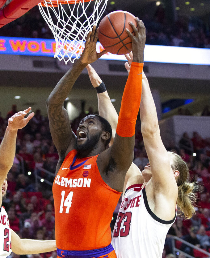 Clemson's Elijah Thomas (14) jumps for a shot in front of North Carolina State's Wyatt Walker (33) during the second half of an NCAA college basketball game in Raleigh, N.C., Saturday, Jan. 26, 2019. (AP Photo/Ben McKeown)