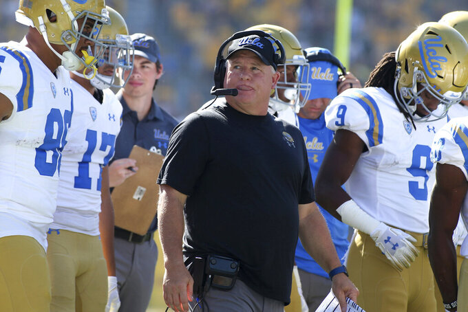 FILE - In this Nov. 10, 2018, file photo, UCLA head coach Chip Kelly, center, walks with his players prior to an NCAA college football game against Arizona State, in Tempe, Ariz. Chip Kelly isn't a fan of momentum and how it can impact a team, but the UCLA coach admitted that the Bruins performance over the second half of last season, that included a win over crosstown rival USC, provided a boost coming into this year.  (AP Photo/Ralph Freso, File)