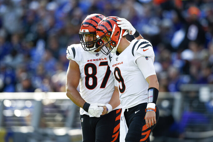 Cincinnati Bengals tight end C.J. Uzomah (87) and quarterback Joe Burrow (9) react after they connected for a touchdown pass during the second half of an NFL football game, Sunday, Oct. 24, 2021, in Baltimore. (AP Photo/Gail Burton)