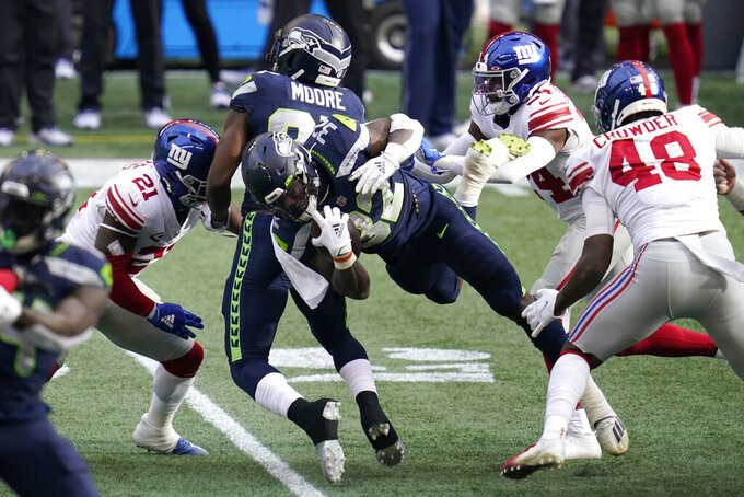 Seattle Seahawks running back Chris Carson (32) dives for yardage as New York Giants safety Jabrill Peppers (21) moves to tackle during the first half of an NFL football game, Sunday, Dec. 6, 2020, in Seattle. (AP Photo/Elaine Thompson)
