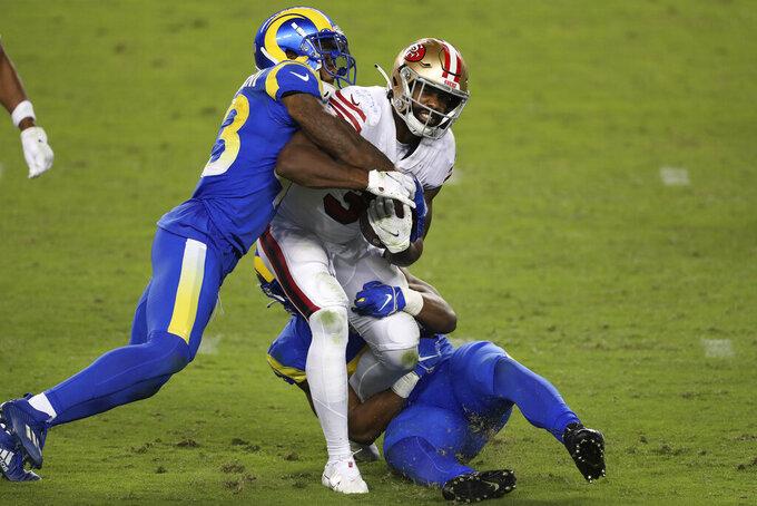 San Francisco 49ers running back Raheem Mostert (31) runs between Los Angeles Rams free safety John Johnson III, left, and middle linebacker Micah Kiser during the first half of an NFL football game in Santa Clara, Calif., Sunday, Oct. 18, 2020. (AP Photo/Jed Jacobsohn)