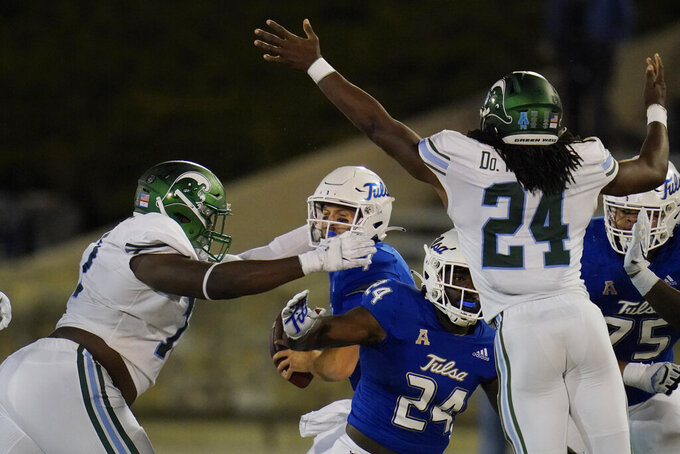 Tulane nose tackle Jeffery Johnson, left, moves in to sack Tulsa quarterback Seth Boomer, center, during the second half of an NCAA college football game in Tulsa, Okla., Thursday, Nov. 19, 2020. (AP Photo/Sue Ogrocki)