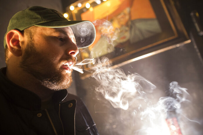 FILE - In this March 29, 2019 file photo, a man smokes marijuana at a Spleef NYC canna-cocktail party in New York. A law that took effect on Aug. 12, 2019 sets the maximum penalty to $50 for possessing less than one ounce of pot. It also turns an unlawful marijuana possession statute into a violation that's similar to a traffic ticket, instead of a criminal charge. (AP Photo/Mary Altaffer, File)