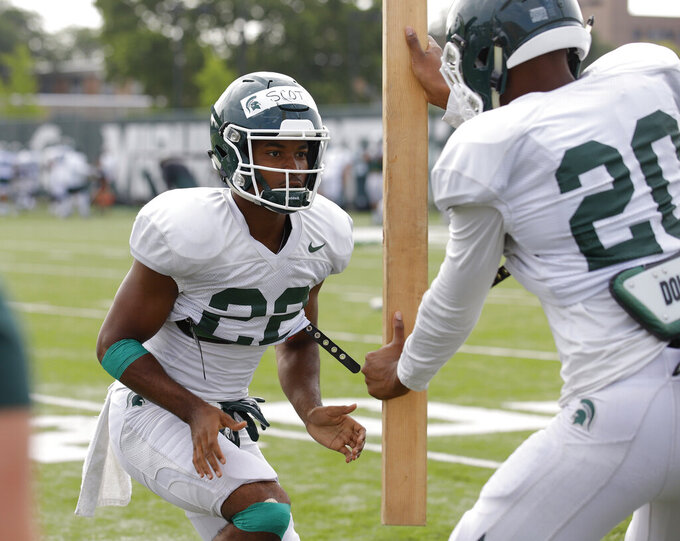 Michigan State cornerback Josiah Scott, left, and cornerback Emmanuel Flowers run a drill during an NCAA college football practice, Monday, Aug. 12, 2019, in East Lansing, Mich. (AP Photo/Al Goldis)
