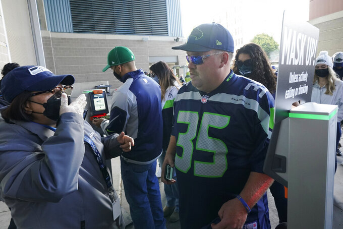 A worker at Lumen Field asks a fan to put on a mask as a precaution due to the COVID-19 pandemic, before an NFL football game between the Seattle Seahawks and the Tennessee Titans, Sunday, Sept. 19, 2021, in Seattle. (AP Photo/Elaine Thompson)