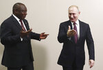 Russian President Vladimir Putin, right, welcomes South Africa's President, Cyril Ramaphosa on the sideline of the Black Sea resort of Sochi, Russia, Wednesday, Oct. 23, 2019. (Sergei Fadeyechev, TASS News Agency Pool Photo via AP)
