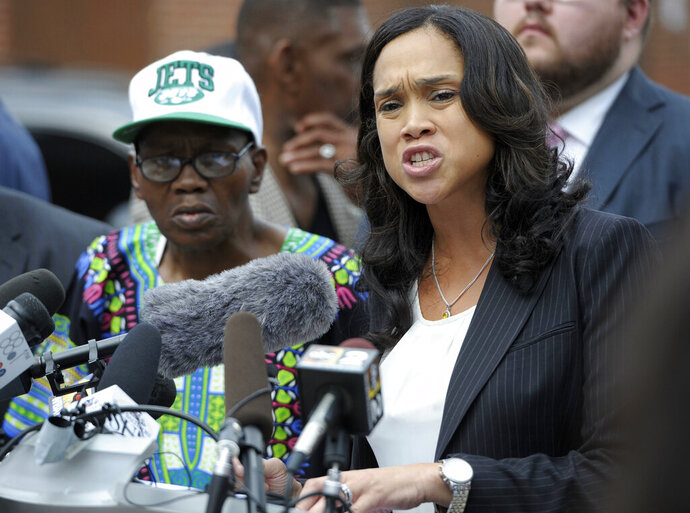 RETRANSMISSION TO CORRECT TO 25 CITY OFFICERS - FILE - In this July 27, 2016 file photo, Baltimore State's Attorney Marilyn Mosby, right, holds a news conference in Baltimore.  Baltimore's top prosecutor has begun asking judges to throw out hundreds of convictions she says were tainted by discredited officers. Mosby's review found a total of 790 criminal cases handled by 25 city officers she says cannot be trusted. (AP Photo/Steve Ruark, File)
