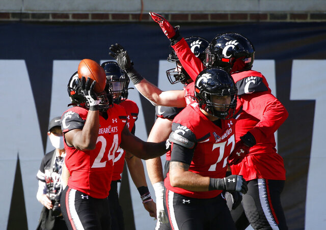 Cincinnati running back Jerome Ford, left, celebrates a touchdown against Memphis during the second half of an NCAA college football game Saturday, Oct. 31, 2020, in Cincinnati. (Photo by Gary Landers)