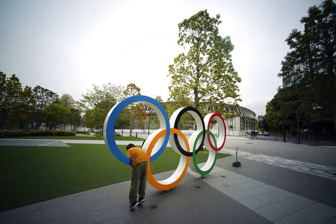 FILE - In this Tuesday, April 21, 2020, file photo, a child plays at the Olympic rings in front of the New National Stadium in Tokyo. A staff member of the Tokyo Olympic organizing committee has tested positive for COVID-19, according to Tokyo organizers in a statement released on Wednesday.  (AP Photo/Eugene Hoshiko, File)